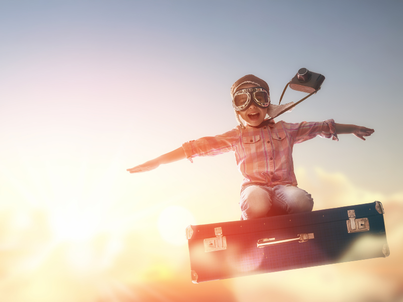 excited young traveler sitting on flying suitcase with arms spreadout like wings