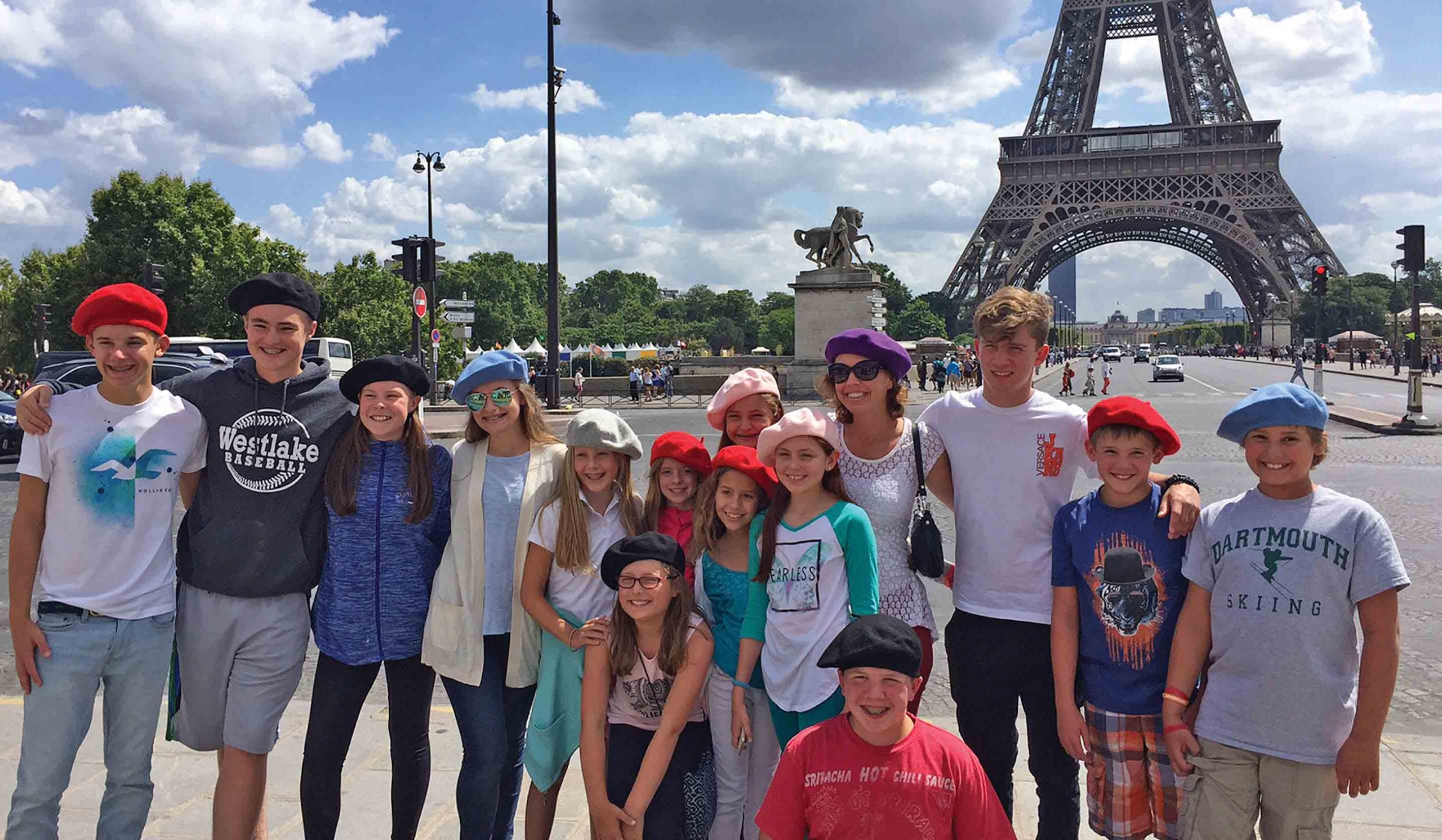 a large family all wearing berets posing in front of Eiffel Tower in Paris during their Tauck tour
